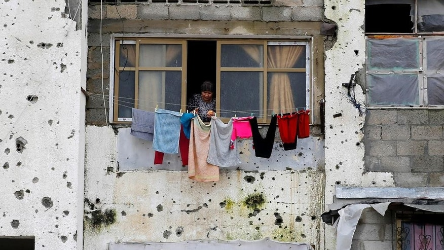 FILE - In this Feb. 22, 2016 photo, a Palestinian woman hangs clothes in a section of a damaged apartment block, which was partially destroyed during the 2014 war between Israel and Hamas, in Beit Lahiya, Gaza Strip. A new report released Monday, April 18, by the World Bank shows that Qatar, the United Arab Emirates and other Arab donors have delivered only a small fraction of aid that was promised to help the devastated seaside enclave after Israel's war against Gaza militants in 2014. (AP Photo/Hatem Moussa, File)