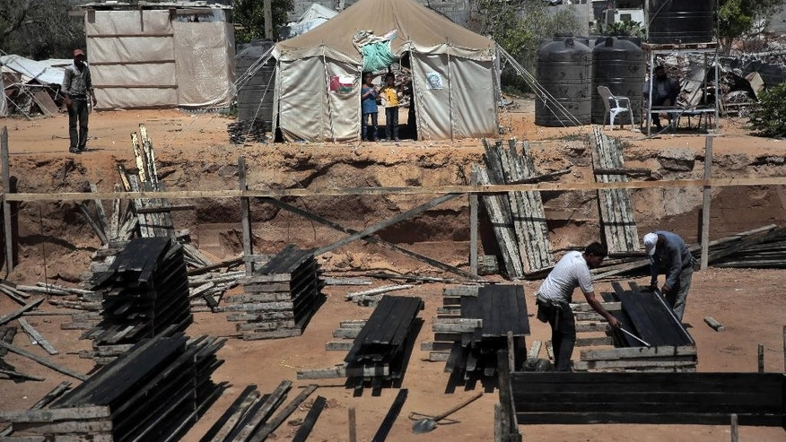 FILE - In this July 23, 2015 photo, two Palestinian boys stand outside a tent, background, watching workers rebuild a house which was destroyed during the 2014 summer war between Israel and Hamas, as the long-awaited reconstruction began in Shijaiyah neighborhood eastern Gaza City. A new report released Monday, April 18, 2016, by the World Bank shows that Qatar, the United Arab Emirates and other Arab donors have delivered only a small fraction of aid that was promised to help the devastated seaside enclave after Israel's war against Gaza militants in 2014. (AP Photo/Khalil Hamra, File)