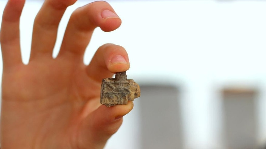 This image released by the Ir David Foundation - City of David on Tuesday, April 19, 2016 shows an ancient Egyptian amulet dating back more than 3,200 years to the days of the Pharaohs discovered by a 12-year-old Israeli girl. Neshama Spielman and her family took part in the Temple Mount Sifting Project, an initiative to sort through earth discarded from the area of the biblical temples in Jerusalem. (Adina Graham, Ir David Foundation - City of David via AP)