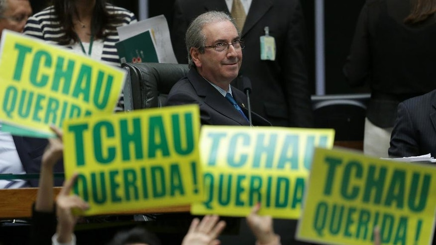 "House Speaker Eduardo Cunha leads the debate on whether or not to impeachment President Dilma Rousseff, as opposition lawmakers hold signs that read in Portuguese ""Goodbye dear"" in the Chamber of Deputies in Brasilia, Brazil, Saturday, April 16, 2016. Sunday's vote will determine whether the impeachment proceeds to the Senate. Rousseff is accused of violating Brazil's fiscal laws to shore up public support amid a flagging economy. If Rousseff is impeached, Cunha is the third in line to take office after the vice president, and has been charged with money laundering and other crimes in the Petrobras scheme. (AP Photo/Eraldo Peres)"