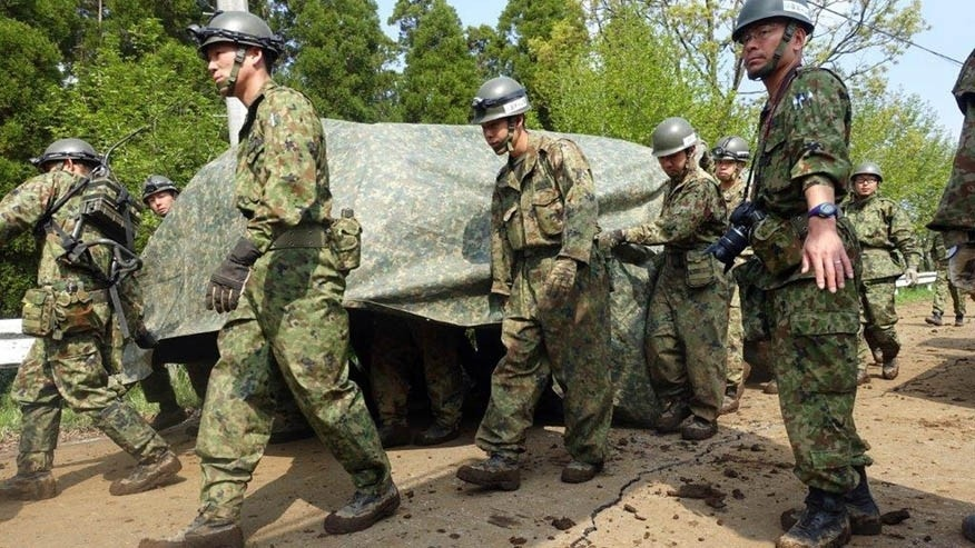 April 19, 2016: Army troops carry at least one body dug up from a mudslide in Minamiaso, Kumamoto prefecture, Japan.