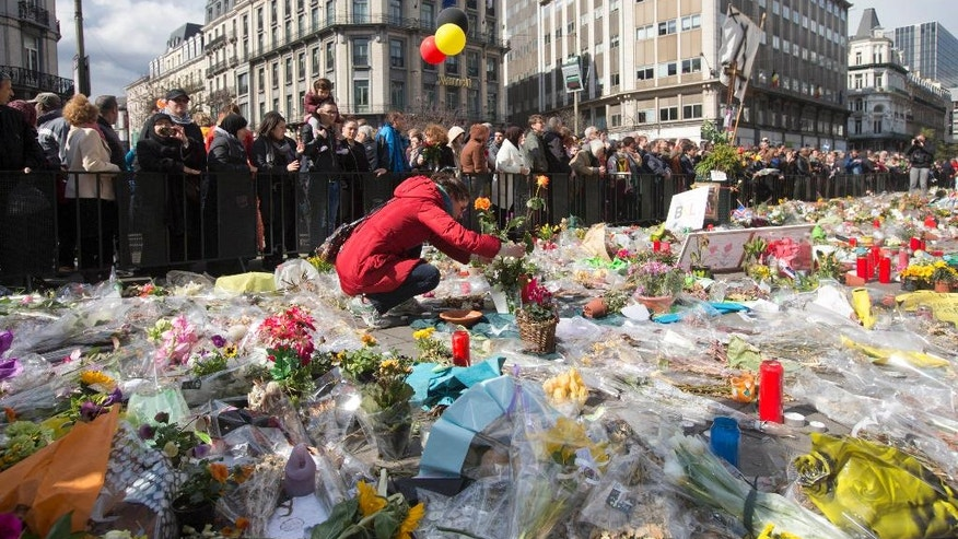 "A woman lays flowers on a memorial to victims of the Brussels attacks during a march against hate in Brussels on Sunday, April 17, 2016. Thousands of people have rallied in Brussels for a ""march against hate"" in the wake of the suicide bombings in the city last month."