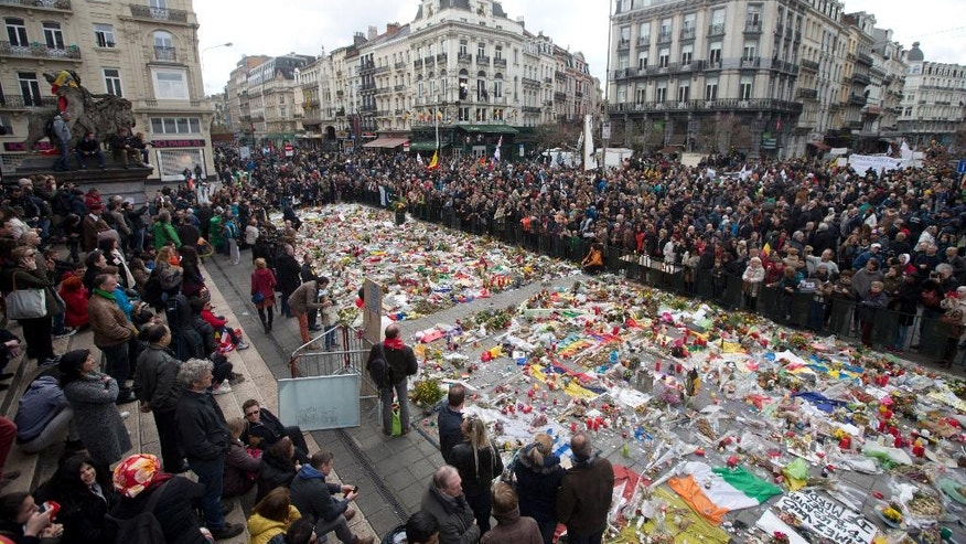 "Marchers gather a memorial to victims of the Brussels attacks during a march against hate in Brussels on Sunday, April 17, 2016. Thousands of people have rallied in Brussels for a ""march against hate"" in the wake of the suicide bombings in the city last month."