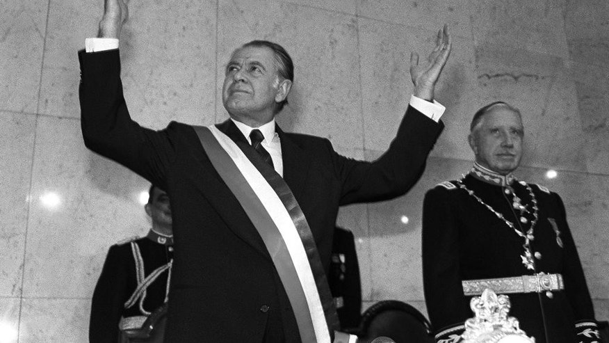 In this March 11, 1990 photo, Chile's newly sworn-in President Patricio Aylwin acknowledges the crowd as Gen. Augusto Pinochet looks on, at Congress in Valparaiso, Chile. Aylwin, who lead Chile's transition from military dictatorship to democracy, died on Tuesday, April 19, 2016, according to the Interior Minister Jorge Burgos. He was 97. (AP Photo/Marco Ugarte)