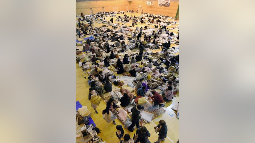 In this April 18, 2016 photo, evacuees take shelter at a gymnasium of a junior high school in Minamiaso, Kumamoto prefecture, Japan. About 100,000 people have left their homes in southern Japan after two shuddering earthquakes on successive nights last week knocked over hundreds of buildings. There is no running water to bathe or flush toilets. Many elderly evacuees sit or lie on futon mattresses that they brought from home. The bedding covers the floor, and there is no privacy. (Yohei Fukai/Kyodo News via AP) JAPAN OUT, MANDATORY CREDIT