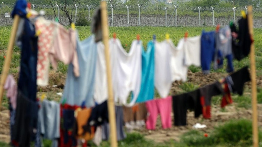 Clothes dry infront of a barbed-wire fence that lines a makeshift camp at the northern Greek border point of Idomeni, Greece, Tuesday, April 19, 2016. More than 11,000 people have been waiting at this border point for over a month hoping it would reopen. (AP Photo/Gregorio Borgia)