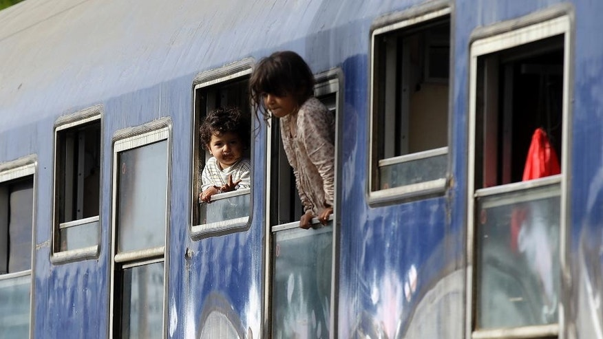 Children peer out from train carriage windows near a makeshift camp at the northern Greek border point of Idomeni, Greece, Tuesday, April 19, 2016. More than 11,000 people have been waiting at this border point for over a month hoping it would reopen. (AP Photo/Gregorio Borgia)