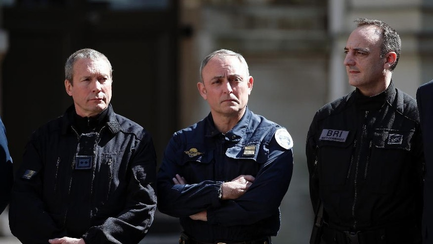 Top elite police chiefs Jean-Michel Fauvergue (RAID), left, Colonel Hubert Bonneau, head of the GIGN gendarme squad, center, and Christophe Molmy (BRI) listen to French Interior Minister Bernard Cazeneuve  in Paris, Tuesday, April 19, 2016. France is reorganizing its police special forces, responding to allegations that rivalries between the three major branches of law enforcement hampered the response to the attacks in November. (AP Photo/Thibault Camus)