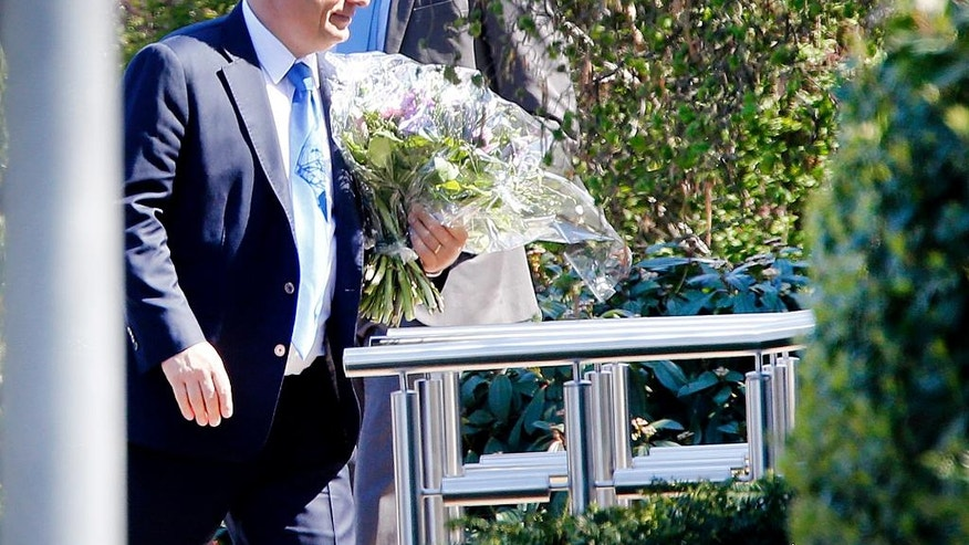 Hungarian Prime Minister Viktor Orban carries flowers as he arrives for a visit to former German Chancellor Helmut Kohl in Kohl's house in Oggersheim, Germany, Tuesday, April 19, 2016. (AP Photo/Michael Probst)