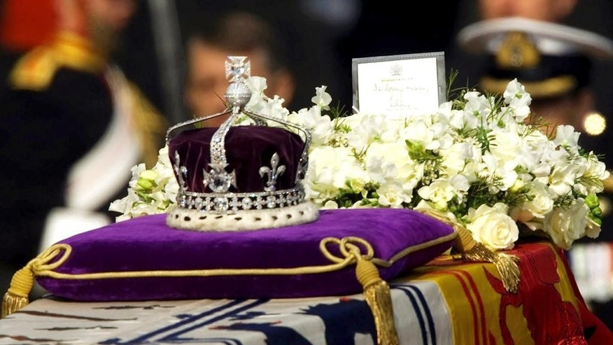 "FILE- in this April 5, 2002 file photo, The Koh-i-noor, or ""mountain of light,"" diamond, set in the Maltese Cross at the front of the crown made for Britain's late Queen Mother Elizabeth, is seen on her coffin, along with her personal standard, a wreath and a note from her daughter, Queen Elizabeth II, as it is drawn to London's Westminster Hall. India's government has told the country's top court it won't try to reclaim the 106-carat Koh-i-Noor diamond, which is now part of the British crown jewels.The government told the Supreme Court on Monday that the diamond was neither taken away forcibly nor stolen, but was given as a gift to Queen Victoria by an Indian king in the mid-19th century. (AP Photo/Alastair Grant, File)"