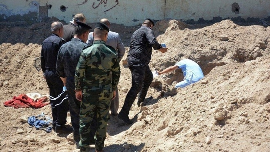 Iraqi security forces including a forensics team work at the site of a mass grave, one of two discovered containing the bodies of dozens of men, women and children killed by Islamic State group militants, in the stadium area in Ramadi, 115 kilometers (70 miles) west of Baghdad, Iraq, Tuesday, April 19, 2016. (AP Photo)