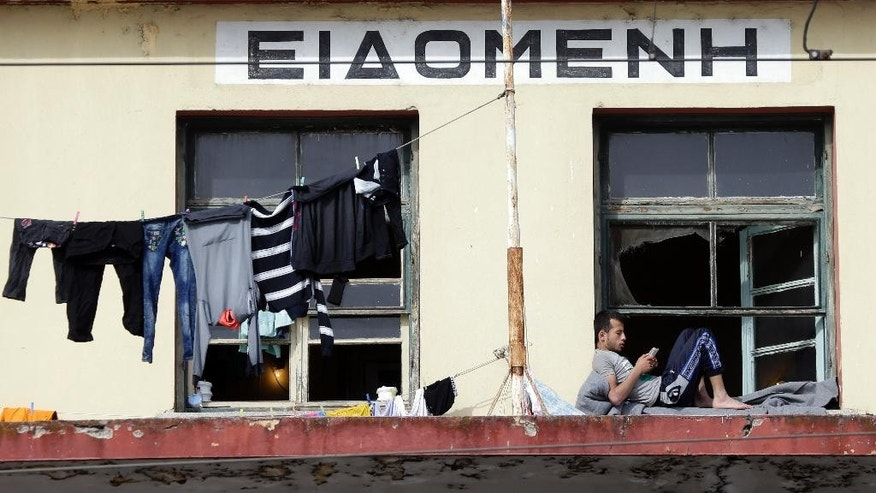 The Greek writing on the Idomeni railway station, towers over a man using his mobile phone at a makeshift migrant camp in the northern Greek border point of Idomeni, Greece, Tuesday, April 19, 2016. Despite appeals from authorities to move to organized shelters, thousands of refugees and migrants have been camped for weeks at Idomeni. They hope that Macedonia will reopen its border and allow them to travel north towards Europe's prosperous heartland. (AP Photo/Gregorio Borgia)