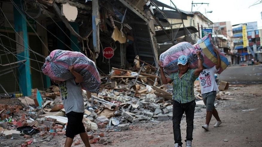 Residents carry items recovered from the rubble of stores, in earthquake ravaged Manta, Ecuador, Monday, April 18, 2016. A Saturday night quake left a trail of ruin along Ecuador's Pacific Ocean coast. Hundreds died and thousands are homeless. (AP Photo/Rodrigo Abd)