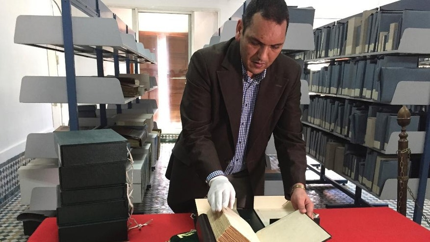 In this April 14, 2016, photo, curator of the Qarawiyyin library, Abdelfattah Bougchouf, opens an original version of Ibn Khaldun's most famous work, Muqadimmah, dating back to the 14th century at the Al-Qarawiyyin mosque in Fez, Morocco, Thursday, April 14, 2016. Founded 12 centuries ago by a pioneering woman, the al-Qarawiyyin library is wrapping up a careful restoration project and King Mohamed VI is expected to preside over the reopening. But authorities haven't decided whether the public will be able to view its treasured Islamic manuscripts, or whether that privilege will be limited to university researchers. (AP Photo/Samia Errazouki)