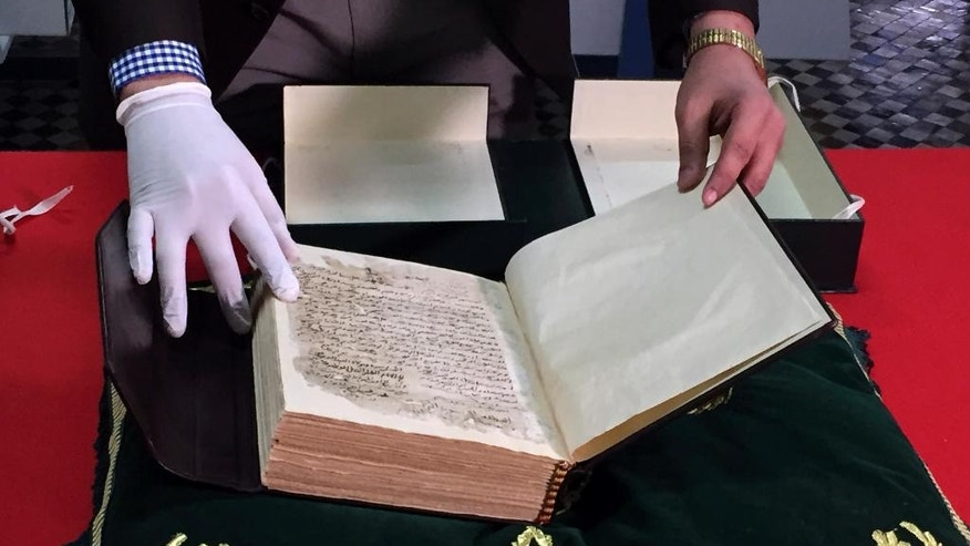 In this April 14, 2016, photo, Abdelfattah Bougchouf, curator of the Qarawiyyin library, opens the first page of an original version of Ibn Khaldun's most famous work, Muqadimmah, dating back to the 14th century at the Al-Qarawiyyin mosque in Fez, Morocco. Founded 12 centuries ago by a pioneering woman, the al-Qarawiyyin library is wrapping up a careful restoration project and King Mohamed VI is expected to preside over the reopening. But authorities haven't decided whether the public will be able to view its treasured Islamic manuscripts, or whether that privilege will be limited to university researchers. (AP Photo/Samia Errazouki)