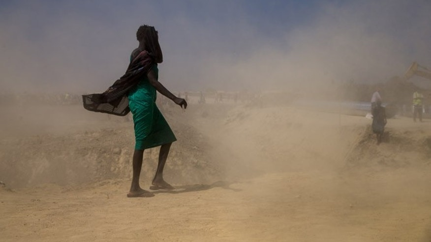Internally displaced woman walks through dust at the Protection of Civilians site in Bentiu, South Sudan. (United Nations)