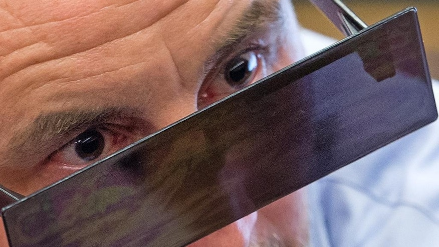 Lutz Bachmann, co-founder of Germany's PEGIDA movement, wears sunglasses as he sits in the courtroom of the local court during the beginning of the trial on accusations of incitement in Dresden, eastern Germany, Tuesday, April 19, 2016. (AP Photo/Jens Meyer/pool)