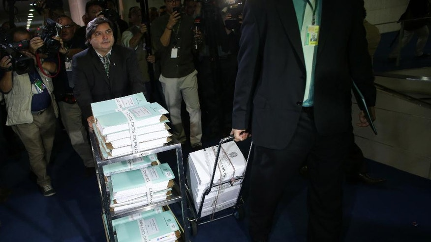 Employees of the Chamber of Deputies carry the volumes of the impeachment process of the Brazil's President Dilma Rousseff, to be delivered to Senate President Renan Calheiros, at the National Congress in Brasilia, Monday, April 18, 2016. The vote late Sunday in favor of impeachment against President Dilma Rousseff proceeds to the Senate, where a majority vote will determine whether Rousseff is put on trial and suspended while Vice President Michel Temer temporarily takes over. (AP Photo/Eraldo Peres)