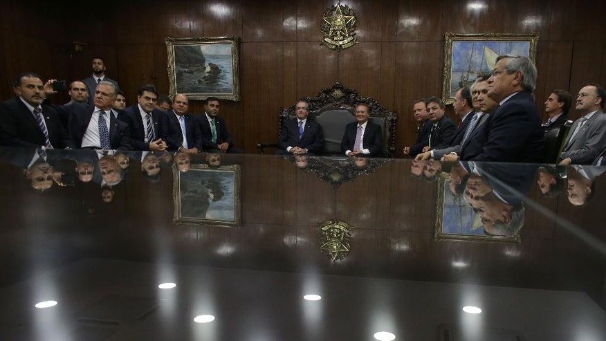 Senate President Renan Calheiros, center right, accompanied by parliamentarians, meets with the President of the Chamber of Deputies Eduardo Cunha, center left, at the National Congress in Brasilia, Monday, April 18, 2016. The vote late Sunday in favor of impeachment against President Dilma Rousseff proceeds to the Senate, where a majority vote will determine whether Rousseff is put on trial and suspended while Vice President Michel Temer temporarily takes over. (AP Photo/Eraldo Peres)