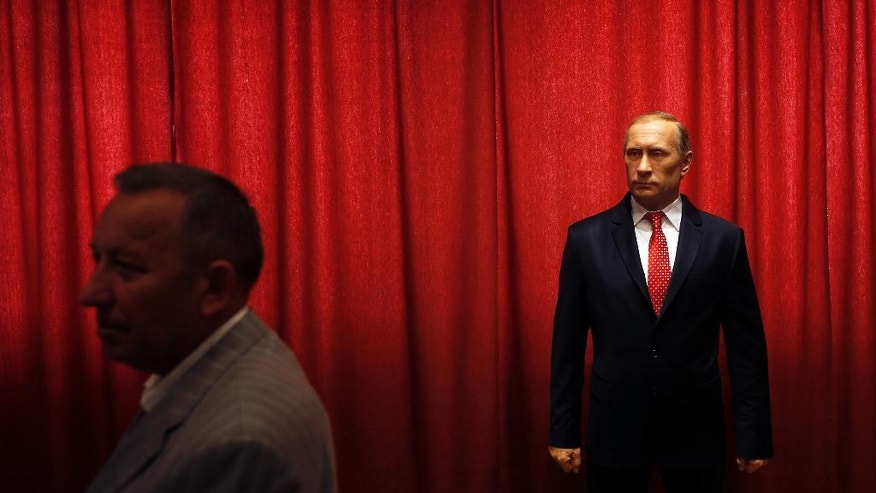 In this photo taken Tuesday, April 12, 2016, a visitor passes by a wax figure of Russian President Vladimir Putin, in a Serbian wax museum in Jagodina. Moscow has been slowly losing its clout in Eastern Europe, as countries have joined NATO and the EU. Most recently, tiny Montenegro has been invited to join the Western military alliance despite strong protests from Russia.  (AP Photo/Darko Vojinovic)