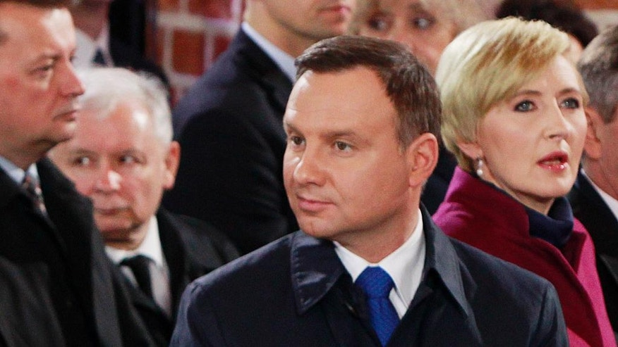 FILE - This file photo from April 14, 2016 shows Poland's President Andrzej Duda, front left, and his wife Agata Kornhauser-Duda, front right, with ruling party Law and Justice leader Jaroslaw Kaczynski sitting behind them during a ceremony marking 1,050 years of the nation's Catholicism in Gniezno, Poland. Kaczynski appears to be snubbing the nation's president, one of his own choice, in what appears to be the first rift in the Law and Justice party since it took power last year. (AP Photo/Czarek Sokolowski, file)