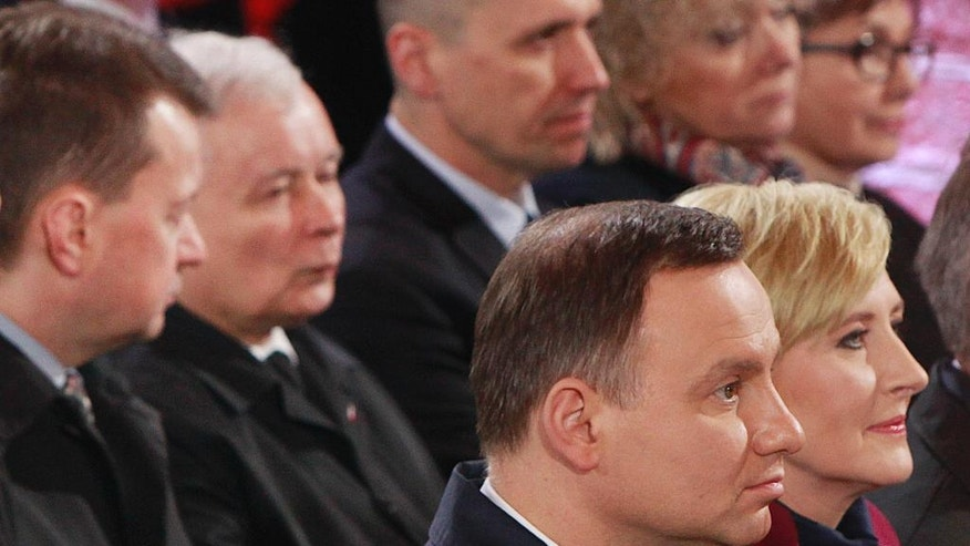 FILE - This file photo from April 14, 2016 shows Poland's President Andrzej Duda, front left, and his wife Agata Kornhauser-Duda, front right, with ruling party Law and Justice leader Jaroslaw Kaczynski sitting behind them during a ceremony marking 1,050 years of the nation's Catholicism in Gniezno, Poland. Kaczynski appears to be snubbing the nation's president, one of his own choice, in what appears to be the first rift in the Law and Justice party since it took power last year. (AP Photo/Czarek Sokolowski)