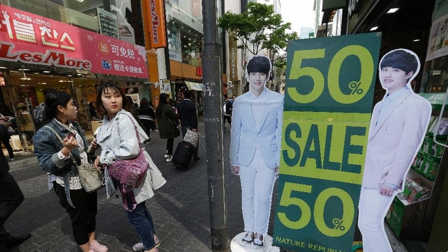 Women stand by a sale sign at a shopping district in Seoul, South Korea, Tuesday, April 19, 2016. South Korea's central bank lowered its growth forecast for Asia's fourth-largest economy on Tuesday, citing the country's weak first-quarter economic performance and a downgrade in the global economic outlook. But it kept its policy rate steady for this month.(AP Photo/Ahn Young-joon)