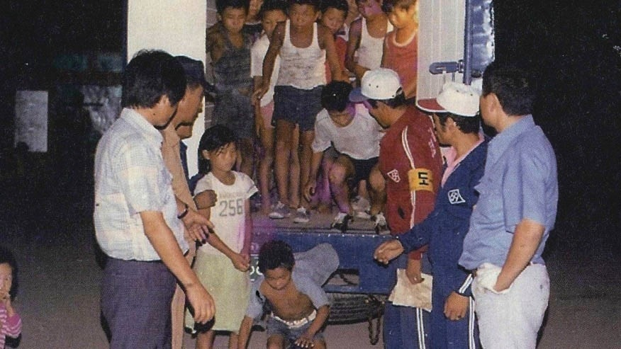 In this undated image provided by the Committee Against Institutionalizing Disabled Persons, a civic group representing the former inmates at the Brothers Home, guards unload children from a truck in Busan, South Korea. An Associated Press investigation shows that rapes and killings of children and the disabled three decades ago at a South Korean institution for so-called vagrants, the Brothers Home, were much more vicious and widespread than previously realized.