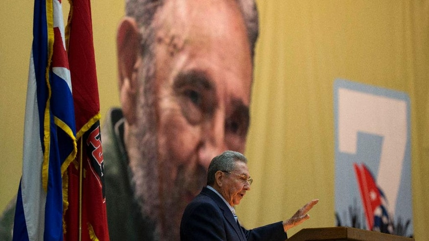 Cuba's President Raul Castro addresses the 7th Cuban Communist Party Congress in Havana, Cuba, Saturday, April 16, 2016, as an image of his brother Fidel Castro is displayed behind.  The Communist Party opened their four-day Congress on Saturday, and are expected to decide the course of the island in the midst of an economic crisis and diplomatic thaw with the United States. The party holds its Congress every five years. (Ismael Francisco/Cubadebate via AP)