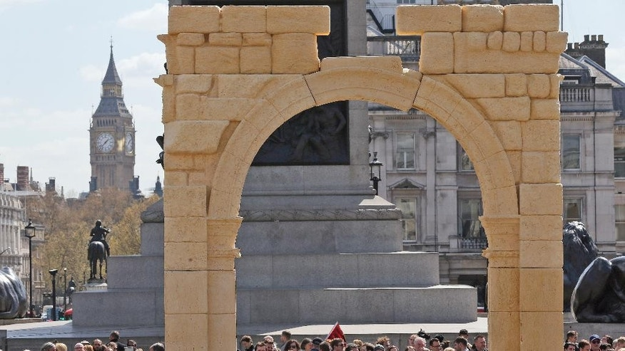An imposing to scale replica of Palmyra's Triumphal Arch in Trafalgar Square is surrounded by people after the Mayor of London, Boris Johnson, and the Executive Director of the Institute for Digital Archaeology (IDA) Roger Michel, unveiled it in London, Tuesday, April 19, 2016. The 5.5m high reconstruction of the 2,000 year old Triumphal Arch from Syria is being installed in the square for three days from Tuesday April 19 until Thursday April 21, to help raise awareness of the importance of historic sites and antiquities as part of World Heritage Week 2016. It will then travel to other cities both inside and outside the Middle East. (AP Photo/Frank Augstein)