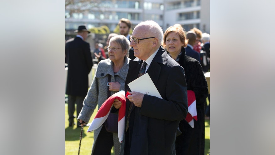 Family members John Howden, center, and Caroline Rowbottom, right, hold flags from the caskets their relatives, WWI soldiers Albert William Venus and Gunner Joseph William Rowbottom, during a burial ceremony at Ypres Extension cemetery in Ypres, Belgium on Wednesday, April 20, 2016. Six WWI British soldiers were laid to rest on Wednesday, more than 100 years after they fell in battle on Flanders Fields. Two soldiers, Gunner Albert William Venus and Gunner Joseph William Rowbottom were both found in Ypres in 2013 and identified through DNA, the other four soldiers remain unidentified. (AP Photo/Virginia Mayo)