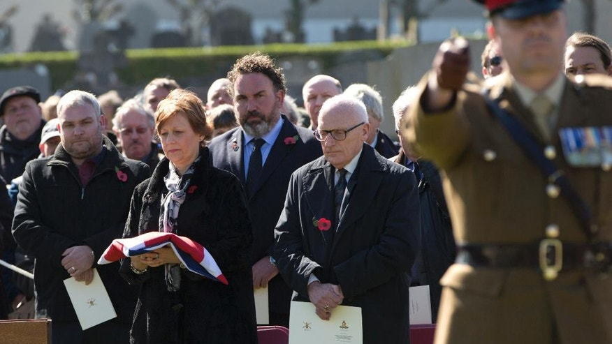 Relative Caroline Rowbottom, left center, holds the flag from the casket of her relative, WWI British soldier Gunner Joseph William Rowbottom, during a burial ceremony at Ypres Extension cemetery in Ypres, Belgium on Wednesday, April 20, 2016. Six WWI British soldiers were laid to rest on Wednesday, more than 100 years after they fell in battle on Flanders Fields. Two soldiers, Gunner Albert William Venus and Gunner Joseph William Rowbottom were both found in Ypres in 2013 and identified through DNA, the other four soldiers remain unidentified. (AP Photo/Virginia Mayo)