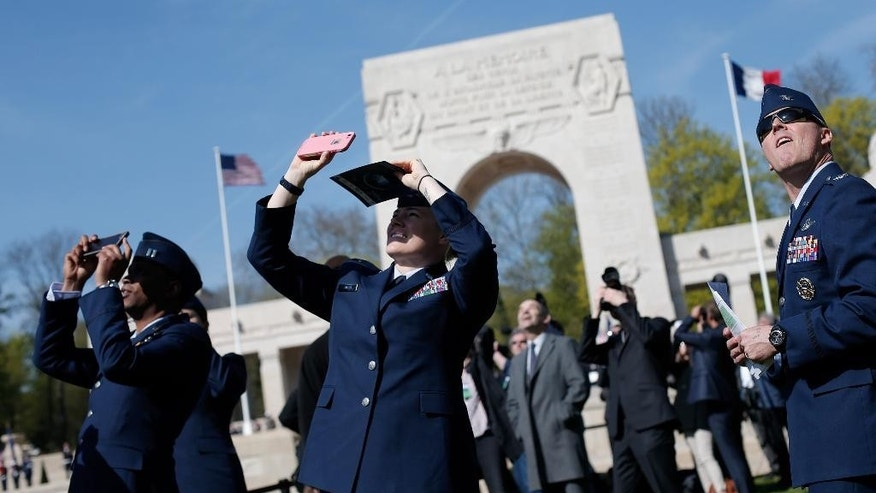 US Air Force soldiers watch an aerial parade during a ceremony honoring the lives of the American pilots who volunteered to fight for France during World War I, in Marne la Coquette, outside Paris, Wednesday, April 20, 2016. The commemoration, which is due to include a fly-by featuring French fighter jets, an American bomber and a biplane, marks the centenary of the formation of the Lafayette Escadrille on April 20, 1916 _ almost a full year before the U.S. entered the war. (AP Photo/Thibault Camus)