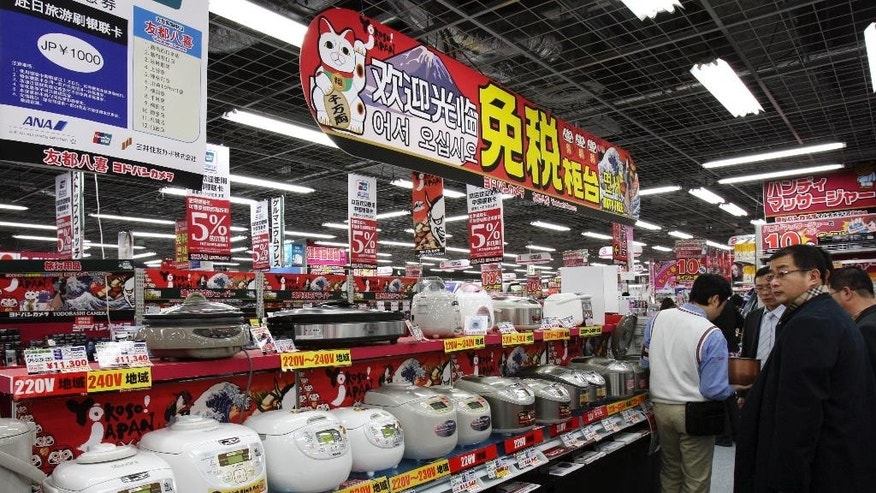 "FILE - In this March 25, 2010, file photo, Chinese customers look at rice cookers displayed under a banner written in Chinese and Korean: ""Welcome, Duty Free counter"" at Yodobashi Camera in Tokyo's Akihabara electronics district. The Chinese government's latest plan to transform itself into a consumer driven economy encourages the production of better consumer appliances, reducing reliance on foreign made goods. (AP Photo/Koji Sasahara, File)"
