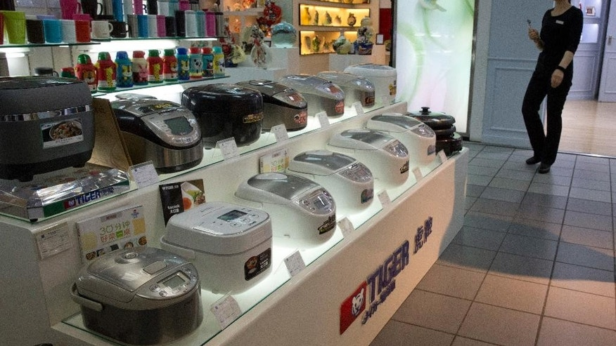 A sales girl past by rice cookers mostly imported from Japan on display at a shopping mall in Beijing, China, Wednesday, April 20, 2016. The Chinese government's latest plan to perk up its slowing economy is based on the humble rice cooker and luxury toilet seats. (AP Photo/Ng Han Guan)