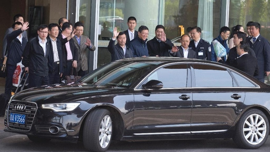 Chinese men waves goodbye as another leave in a car after exiting from the VIP exit of the Beijing Capital airport usually reserved for officials and other dignitaries returning from overseas in Beijing, China, Wednesday, April 20, 2016. Amid an ongoing austerity drive, China's Finance Ministry says official spending on overseas travel, vehicles and entertainment was almost 15 percent less than budgeted last year. (AP Photo/Ng Han Guan)