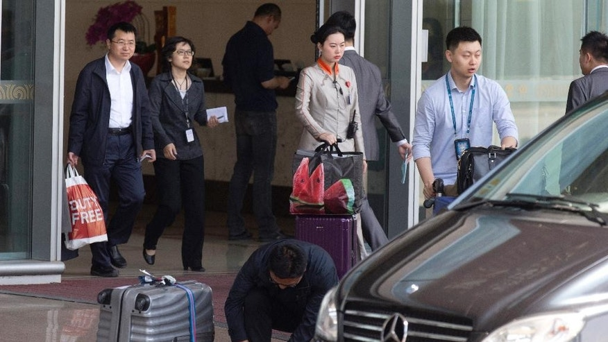 Chinese staff transfer pieces of luggage from the VIP exit of the Beijing Capital airport that is usually reserved for officials and other dignitaries returning from overseas in Beijing, China, Wednesday, April 20, 2016. Amid an ongoing austerity drive, China's Finance Ministry says official spending on overseas travel, vehicles and entertainment was almost 15 percent less than budgeted last year. (AP Photo/Ng Han Guan)
