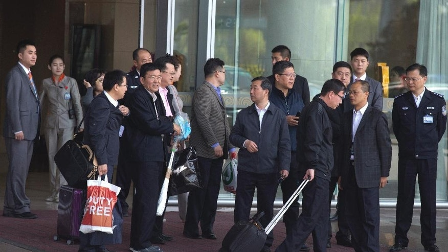 Chinese men leave from the VIP exit of the Beijing Capital airport usually reserved for officials and other dignitaries returning from overseas in Beijing, China, Wednesday, April 20, 2016. Amid an ongoing austerity drive, China's Finance Ministry says official spending on overseas travel, vehicles and entertainment was almost 15 percent less than budgeted last year. (AP Photo/Ng Han Guan)