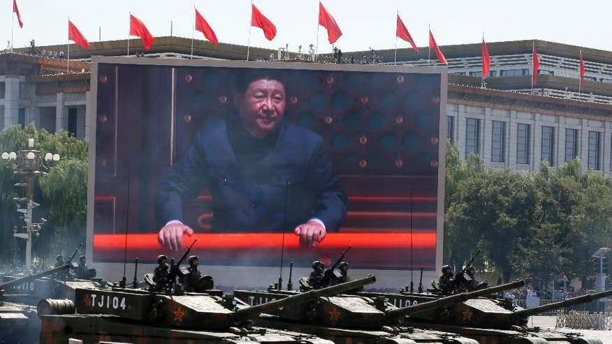 FILE - In this Thursday, Sept. 3, 2015 file photo, Chinese President Xi Jinping is displayed on a screen as Type 99A2 Chinese battle tanks take part in a parade commemorating the 70th anniversary of Japan's surrender during World War II held in front of Tiananmen Gate in Beijing. Chinese President Xi Jinping is assuming a more direct role as commander of the country's powerful armed forces with the new title of commander in chief of its Joint Operations Command Center, as revealed in news reports run on Wednesday, April 20, and Thursday, April 21, 2016, in which he appeared publicly for the first time in camouflage battle dress wearing the center's insignia.(AP Photo/Ng Han Guan, File)