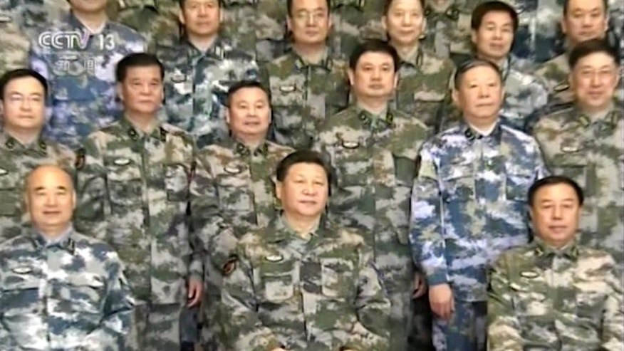 In this Thursday, April 21, 2016 image taken from a video footage run by China's CCTV via AP Video, Chinese President Xi Jinping, center, in military uniform poses for a group photo with military staff members at the Chinese army's Joint Operation Command Center in Beijing. Xi is assuming a more direct role as commander of the country's powerful armed forces with the new title of commander in chief of its Joint Operations Command Center. Xi's new position was revealed in news reports run on Wednesday and Thursday in which he appeared publicly for the first time in camouflage battle dress wearing the center's insignia. (CCTV via AP Video) CHINA OUT, TV OUT, NO SALES, EDITORIAL USE ONLY