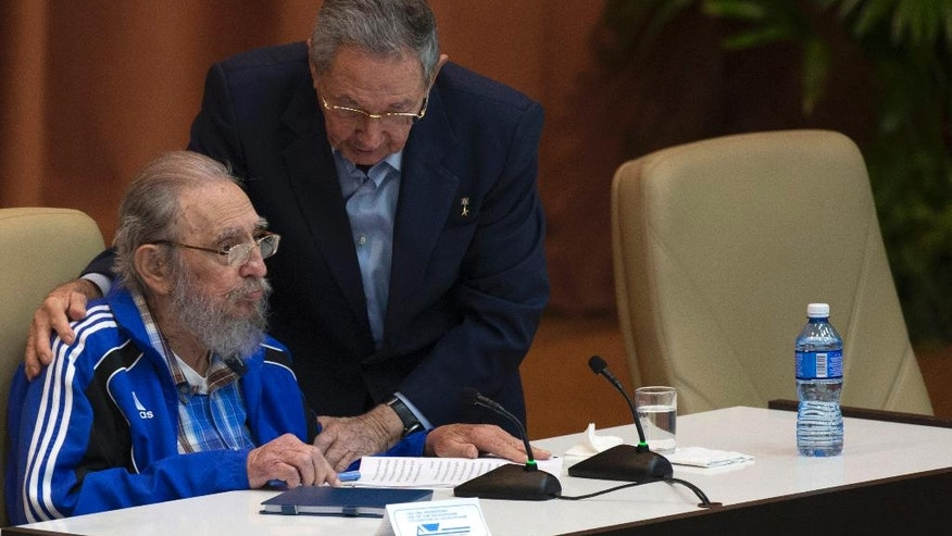 Cuba's President Raul Castro, right, embraces his brother Fidel as he leans over to speak with him during the last day of the 7th Cuban Communist Party Congress in Havana, Cuba, Tuesday, April 19, 2016. Fidel Castro formally stepped down in 2008 after suffering gastrointestinal ailments and public appearances have been increasingly unusual in recent years. (Ismael Francisco/Cubadebate via AP)