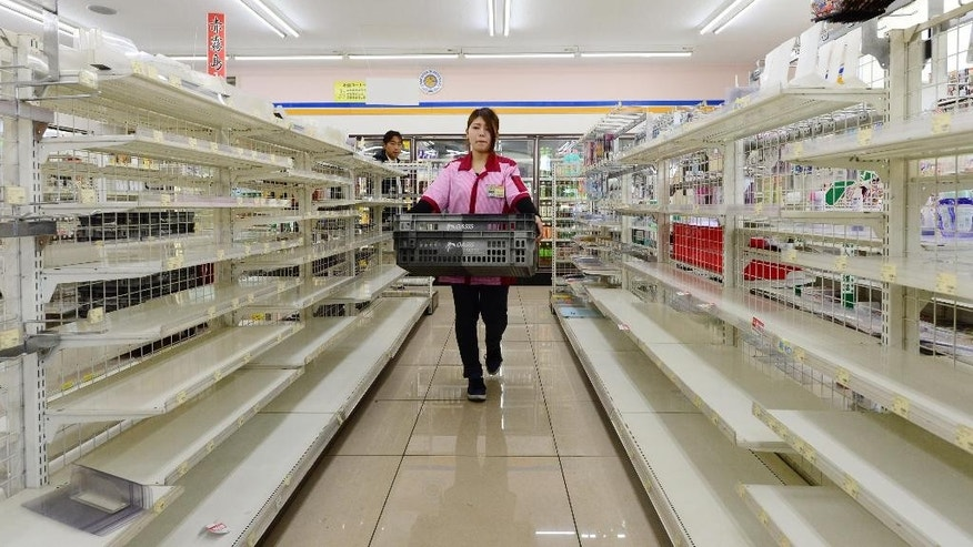 An employee walks through the empty shelves selling food at a store in Kumamoto, Japan Wednesday, April 20, 2016. Many residents were still recovering from the shock of the destruction by earthquakes, while struggling to bring their lives, and spirit, together. (Koki Sengoku/Kyodo News via AP JAPAN OUT, MANDATORY CREDIT