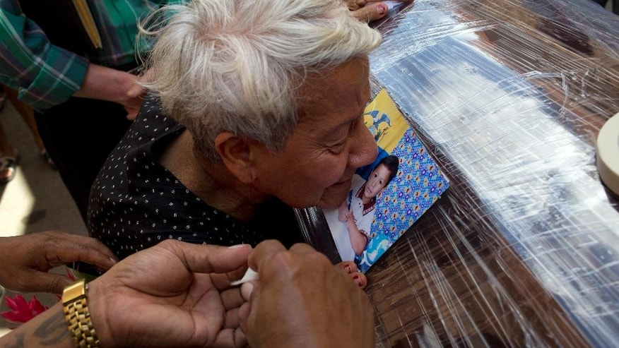 A relative kisses a photo of Kexly Valentino affixed to her coffin, in Montecristi, Ecuador, Tuesday, April 19, 2016. Kexly died along with her mother Gabriela and her brother Alex during the 7.8-magnitude earthquake that hit Ecuador's Pacific coast on Saturday. (AP Photo/Rodrigo Abd)