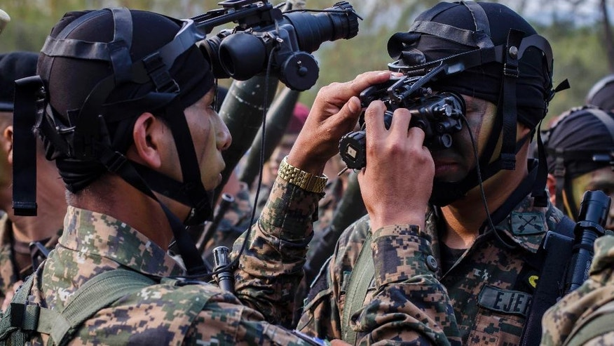 El Salvador army special forces try on their night vision goggles during a presentation to the press as part of a new stepped-up phase in the government's fight against gangs in San Salvador, El Salvador, Wednesday, April, 20, 2016. The government of El Salvador is deploying a force of 1,000 soldiers and police to fight gangs in rural areas. The force will operate with helicopters, night-vision devices and machine guns and it will go after an estimated 100 leaders of the Mara Salvatrucha and Barrio 18 gangs. (AP Photo/Salvador Melendez)