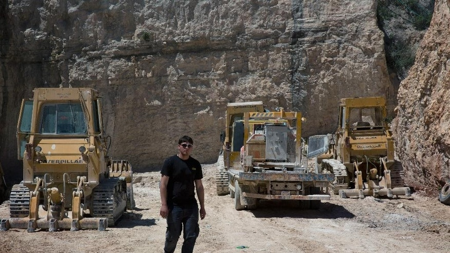 In this Tuesday, April 19, 2016 photo, 25 year-old, Alaa Al-Tawil, walks through a Palestinian quarry in the West Bank village of Beit Fajar, Bethlehem. The economic future of the Palestinian town of Beit Fajar looks bleak after Israel's military shut some three dozen quarries and put 3,500 jobs at risk, paralyzing the dominant local industry. (AP Photo/Nasser Nasser)