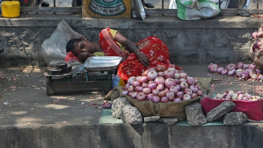 An Indian vendor selling onions on a sidewalk rests under the shade of a tree on a hot summer day in Hyderabad, India, Wednesday, April 20, 2016. Weeks of sweltering temperatures have caused more than 160 deaths in southern and eastern India, officials said Tuesday, warning that any relief from monsoon rains was still likely weeks away. Most of the heat-wave victims were laborers and farmers in the states of Telangana, Andhra Pradesh and Orissa, though temperatures elsewhere in India have also hit 45 degrees Celsius (113 Fahrenheit).(AP Photo/Mahesh Kumar A.)