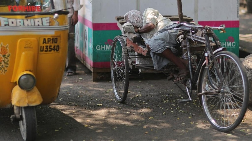 An Indian rickshaw puller rests under the shade of a tree on a hot summer day in Hyderabad, India, Wednesday, April 20, 2016. Weeks of sweltering temperatures have caused more than 160 deaths in southern and eastern India, officials said Tuesday, warning that any relief from monsoon rains was still likely weeks away. Most of the heat-wave victims were laborers and farmers in the states of Telangana, Andhra Pradesh and Orissa, though temperatures elsewhere in India have also hit 45 degrees Celsius (113 Fahrenheit).(AP Photo/Mahesh Kumar A.)