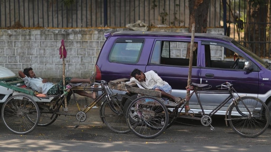 Indian rickshaw pullers rest under the shade of a tree on a hot summer day in Hyderabad, India, Wednesday, April 20, 2016. Weeks of sweltering temperatures have caused more than 160 deaths in southern and eastern India, officials said Tuesday, warning that any relief from monsoon rains was still likely weeks away. Most of the heat-wave victims were laborers and farmers in the states of Telangana, Andhra Pradesh and Orissa, though temperatures elsewhere in India have also hit 45 degrees Celsius (113 Fahrenheit).(AP Photo/Mahesh Kumar A.)