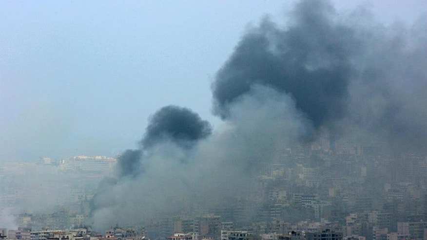 """FILE - In this Sunday July 16, 2006 file photo, black smoke rises from the demolished headquarters of Hezbollah in the suburbs of Beirut, Lebanon, following Israeli air strikes. A top Israeli military leader on Wednesday April 20, 2016, issued a stern warning to the Lebanese militant group Hezbollah, saying any future war between the two enemies will unleash """"devastating"""" damage on Lebanon. (AP Photo/Kevork Djansezian, File)"""