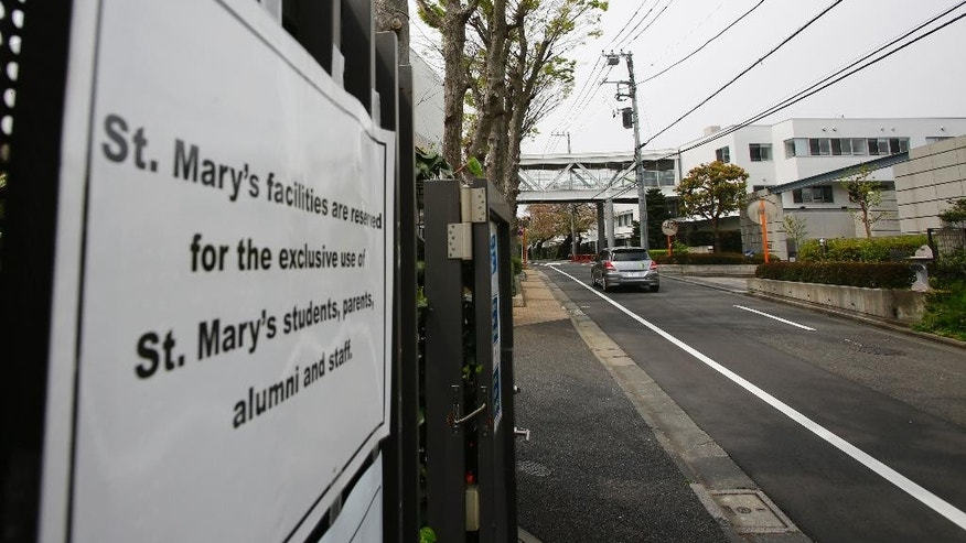 In this Sunday, April 10, 2016, photo, a car passes by St. Mary's International School in Tokyo. The Roman Catholic Church's worldwide sex abuse scandal has stretched into one of the world's least Catholic countries: Japan. Former students at a prestigious all-boys parochial school allege they were molested or raped by religious brothers who taught there decades ago. One former student says he was raped in the chapel by two brothers when he was 11. (AP Photo/Shizuo Kambayashi)